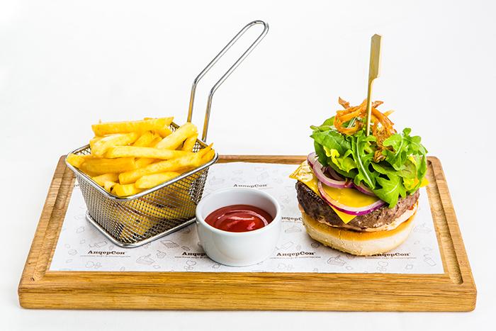 Бургер из говядины с сыром чеддер на хрустящей булочке, подается с картофелем фри и клюквенным соусом